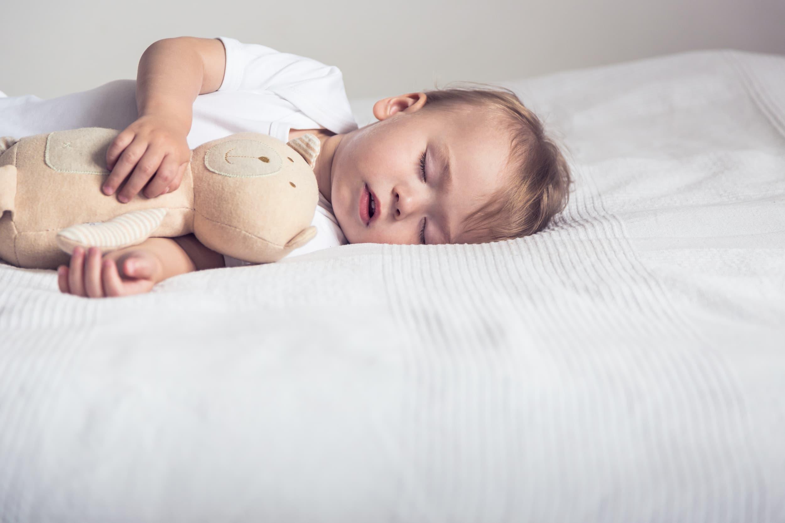Baby boy sleeping on a bed with teddy bear