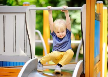 Little boy having fun on outdoor playground/on slide. Summer active sport leisure for kids