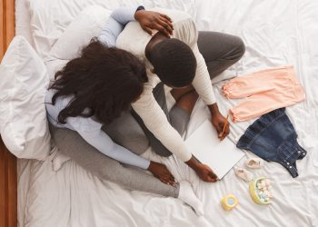 Young couple sitting on a bed doing a pregnancy plan