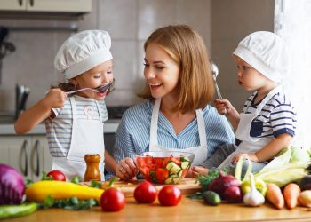 Young mother with her two children cooking in the kitchen