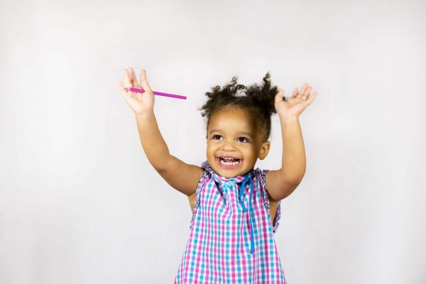 Waist-up portrait of happy african american baby girl holding hands up and laughing. Little child with wide smile and bright dress. Isolated on white background